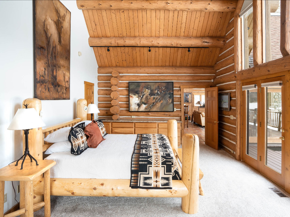 Stage Stop bedroom with large western artwork and log features